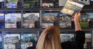 A woman looking at houses for sale in an estate agents Photograph: David Cheskin/PA
