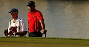 Tiger Woods waits on the 18th green alongside his caddie Joe LaCava during the final round of the World Golf Championships-Cadillac Championship. Photograph:  Scott Halleran/Getty Images