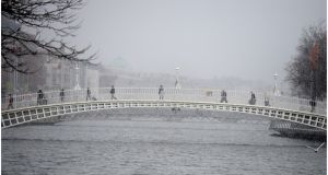 Pedestrians struggle over the Ha'penny Bridge in Dublin yesterday. Photograph: Bryan O'Brien /The Irish Times