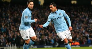 Manchester City's  Carlos Tevez (right) has been charged over driving offences. Photograph:   Alex Livesey/Getty Images