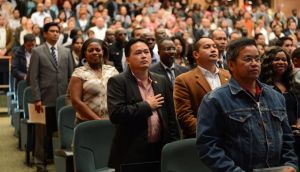 New citizens listen to the National Anthem at a Citizenship Ceremony in the National Convention Centre Dublin. Photograph: Frank Miller / The Irish Times