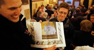 Seminary students from Australia hold a special edition of the Vatican newspaper Osservatore Romano to diners from Ireland, in Rome yesterday. Jorge Mario Bergoglio of Argentina was elected in a surprise choice to be the new pope. Photograph: Chris Helgren/Reuters