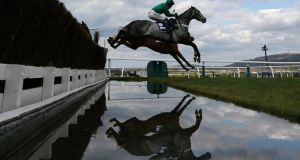 Horses jump a water fence during the Novices' Steeple Chase  yesterday. Photograph: Stefan Wermuth/Reuters