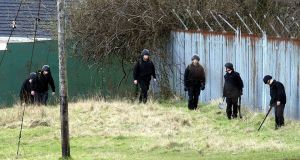 Army bomb disposal experts search the area where a suspected mortar bomb was discovered. The device was found close to New Barnsley station in north Belfast this morning. Photograph: Paul Faith/PA Wire