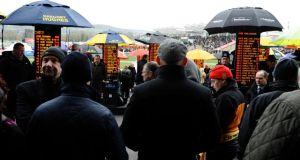 Punters check out the odds during Cheltenham Gold Cup Day. Photograph: Alan Crowhurst (Getty Images)