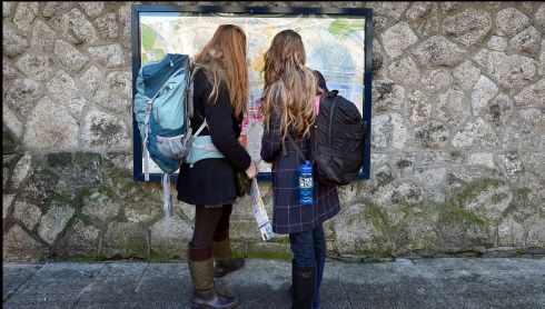 Tourists in Dublin for the St Patrick's festival look at a map outside the Tourist office on Suffolk Street. Photograph: Brenda Fitzsimons/The Irish Times