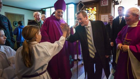 Taoiseach Enda Kenny with Rev Nicholas DiMarzio (left), Bishop of Brooklyn, and Monsignor Michael J. Curran (right), pastor of St. Thomas More Church, hi-fives an altar girl as he arrives for St Patrick's Day Mass. Photograph:  Michael Nagle/Getty Images