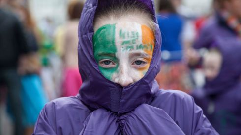 A member of Ascension Baton Twirlers keeps warm before taking part in the parade as part of the St Patrick's Festival in Cork City.  Photograph: Clare Keogh