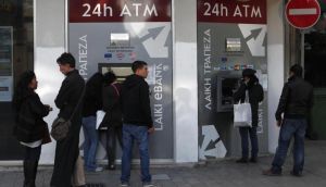 People wait to use the ATM machines outside a Laiki Bank branch in the Cypriot capital  Nicosia yesterday. Photograph: Petros Karadjias