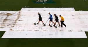Groundsmen push water off covers on the final day of the second  Test between New Zealand and England in Wellington. Photograph:  David Gray/Reuters