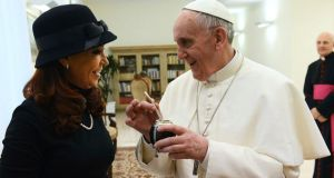 Pope Francis holds a traditional calabash gourd used to drink Mate, which was given to him as a present from President Cristina Kirchner yesterday. Photograph: Argentine Presidency via New York Times