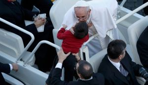 Pope Francis kisses a child as he arrives in Saint Peter's Square for his inaugural mass at the Vatican this morning. Photograph: Tony Gentile/Reuters