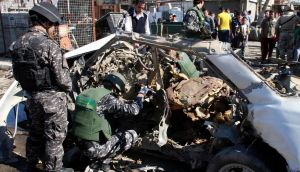 Iraqi policemen examine the remains of a car bomb in Baghdad's Sadr City today. Photograph: Qahtan al-Sudani/Reuters