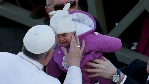 Pope Francis kisses a child as he arrives in Saint Peter's Square for his inaugural mass at the Vatican.  Photograph: Tony Gentile/Reuters