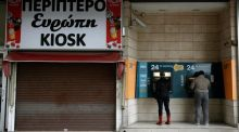 Bank customers make transactions at an automated teller machine (ATM) outside a closed branch of the Bank of Cyprus in Nicosia. Photograph: Yorgos Karahalis/Reuters