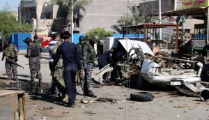 Iraqi policemen examine the remains of a car bomb in Baghdad's Sadr City yesterday. A series of co-ordinated car bombs and blasts hit Shia  districts across Baghdad and south of the Iraqi capital, killing at least 50 people on the 10th anniversary of the US-led invasion. Photograph: Qahtan al-Sudani/Reuters
