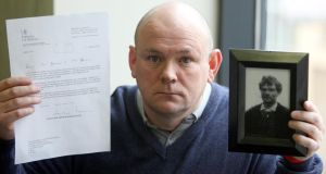 Charlie Agnew, nephew of John Pat Cunningham,  with the  apology from the British ministry of defence and a picture of Mr Cunningham at a press conference in Belfast yesterday. Photograph: Paul Faith/PA