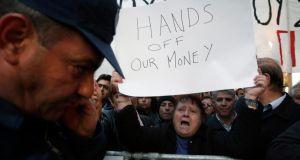 Protesters shout slogans during an anti-bailout rally outside the parliament in Nicosia. Photograph: Reuters