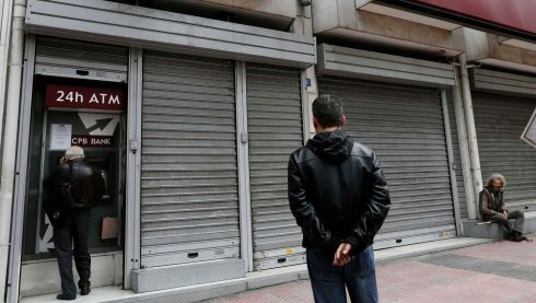 People wait to make transactions at an ATM machine as a man (right) begs outside a closed Cyprus Popular Bank (CPB) branch in Athens. Photograph: John Kolesidis/Reuters