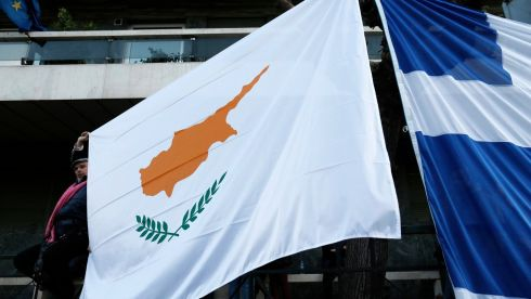 A protester holds a Cypriot flag next to a Greek flag during a rally against a levy on bank deposits in Cyprus, outside of the European Union office in Athens. Photograph: John Kolesidis/Reuters