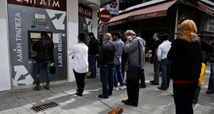 People queue up to make a transaction at an ATM outside a branch of Laiki Bank in Nicosia, Cyprus today. Photograph: Yannis Behrakis/Reuters.