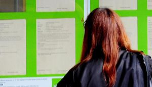 A young  woman looking into the window of a job centre in Britain: Almost 12,000 teenagers in Britain, aged 13-16, were offered a choice of 69 possible future careers: the single most popular one among 13-14 year olds is acting, with a life in sports, or in military uniform also featuring highly