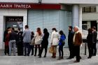 People queue to make transactions at an ATM outside a branch of Laiki Bank in Nicosia.  Photograph: Yannis Behrakis/Reuters