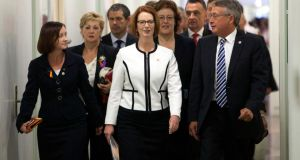 Australian Prime Minister Julia Gillard (C) walks with her supporters, including Treasurer Wayne Swan (R), to a meeting at Parliament House in Canberra. Photograph: Reuters