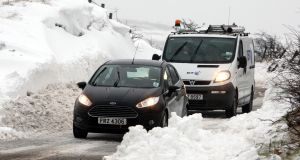 Motorists make their way through snow covered roads,on the Carnlough to Ballymena road in Co Antrim after sbnow ploughs cleared drifting snow. Photograph: Paul Faith/PA Wire