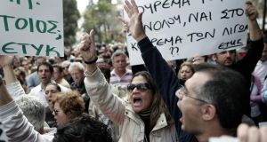Protesting employees of Laiki bank chant slogans outside the Cypriot parliament yesterday. Cypriot authorities were last night  putting the final touchesto a plan they hope will convince international lenders to provide the money the country urgently needs to avoid bankruptcy within days. Photograph: Petros Giannakouris/AP
