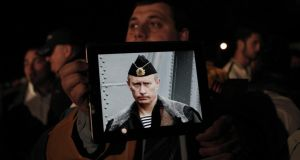 A Russian resident in Cyprus holds a tablet with a picture of Russian president Vladimir Putin during a protest outside the Cypriot parliament yesterday. Photograph: Petros Giannakouris/AP