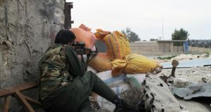 A Free Syrian Army fighter takes position behind sandbags in Aleppo earlier this week. Photograph: Abdalghne Karoof/Reuters