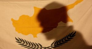 A protester casts his shadow onto a Cypriot flag during an anti-bailout rally outside the presidential palace in Nicosia. Photograph: Yorgos Karahalis/Reuters