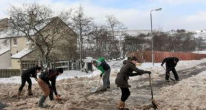Residents clear the road of snow to gain access to their houses as wintry weather continues to cause havoc  in the village of Cargan in the Glens of Antrim. Photograph: Reuters