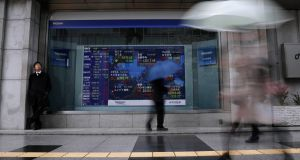 Passers-by walk past a stock index board showing various countries' stock price index outside a brokerage in Tokyo today. Photograph: Reuters