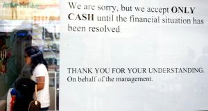 A sign in a Nicosia shop window yesterday informs shoppers that only cash will be accepted. Some analysts have suggested Cyprus's GDP could fall by 20 per cent over the next few years as a result of the bank restructuring plan. Photograph: Milos Bicanski/Getty Images