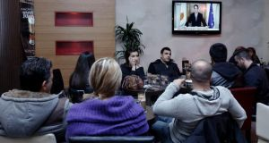 Cypriots watch in a Nicosia cafe as President Nicos Anastasiades addresses the nation yesterday following the agreement of a bailout deal with the European Union and International Monetary Fund. Photograph: Reuters