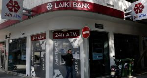 A man leaves a Laiki Bank ATM in Nicosia. All banks in Cyprus will remain shut until Thursday, the country's finance minister has ordered. Photograph: Yorgos Karahalis /Reuters