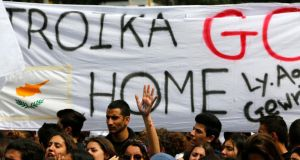 Students take part in an anti-troika protest outside the presidential palace in Nicosia today. The chairman of Cyprus's biggest commercial bank offered his resignation and thousands of students protested in the capital as banks stayed shut to stop a run on deposits. Photograph: Yannis Behrakis/Reuters