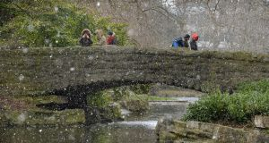 Pedestrains caught in snow flurrys in Dublin's Stephens Green today .Photograph: David Sleator/The Irish Times