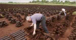 John Kehoe (left) and James Connolly stack turf to dry on a bog near Portarlington, Co Laois. Bord na Móna says sales of peat briquettes have risen by nearly half on 2012 figures. Photograph: Alan Betson
