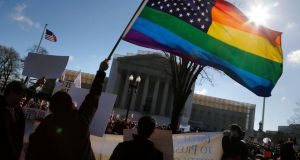 Anti-Proposition 8 protesters wave a rainbow flag in front of the US supreme court in Washington, yesterday. Photograph: Jonathan Ernst/Reuters