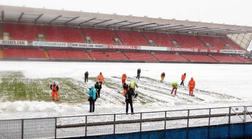 Ground staff help clear snow away from Windsor Park prior to the Fifa World Cup 2014 Qualifier this evening. Photograph: Paul Faith/PA