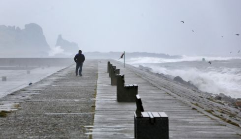 A walker braves the wind and rain in Howth this afternoon. Photograph: Collins