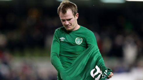 A dejected Glenn Whelan removes his jersey as he walks off the pitch after the game. Photograph: James Crombie/Inpho.