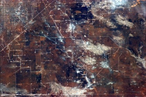 Oil drilling draws a circuit board on the ochre landscape. Photographs: Chris Hadfield