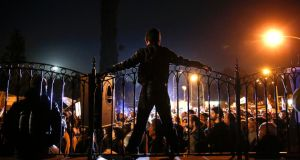 A protester atop the fence at the presidential palace during an anti-bailout rally in Nicosia yesterday. Photograph: Yannis Behrakis/Reuters