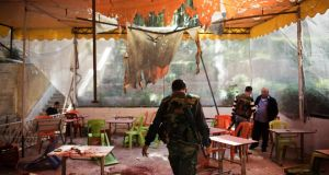 Syrian soldiers and investigators at an outdoor cafe that was hit by mortar shells at Damascus University yesterday in which about 20 students died. Photograph: Andrea Bruce/New York Times