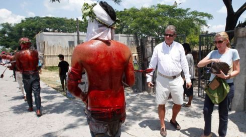 Tourists watch as penitents, bloodied after self-flagellation, walk during a Good Friday crucifixion re-enactment in the Philippines. Photograph: Romeo Ranoco/Reuters