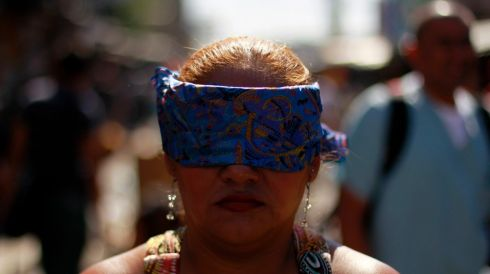 A woman walks blindfolded while performing penance in San Salvador. Photograph: Ulises Rodriguez/Reuters